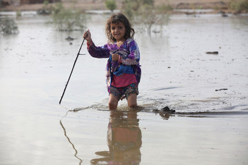 A girl plays in floodwater at a camp for internally displaced people in the Dhanah area of the central province of Marib, Yemen