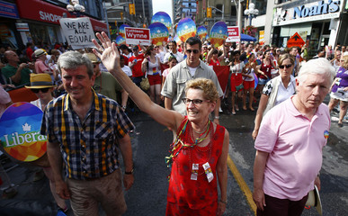 """Wynne marches with former politician Bob Rae (R) during the"""" WorldPride"""" gay pride Parade in Toronto"""