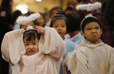 Children dressed as angels react as they attend a Christmas mass at a Catholic church in Beijing