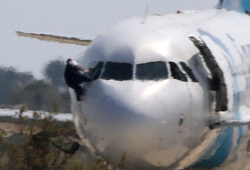 An unidentified man struggles with another as he climbs out of the cockpit window of the hijacked Egyptair Airbus A320 at Larnaca Airport in Larnaca, Cyprus