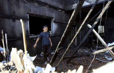 Palestinian boy inspects a house that was badly damaged from a suspected attack by Jewish extremists on two houses at Kafr Duma village near Nablus