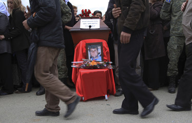 Kosovo Albanians pay respects to family members during a reburial ceremony of the remains of 19 Albanians who were killed during the Kosovo War and identified from a mass grave in the village of Krusha e Vogel