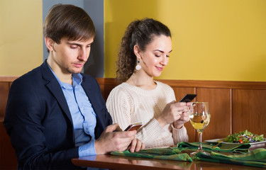 engaged young man sitting with his girlfriend at restaurant