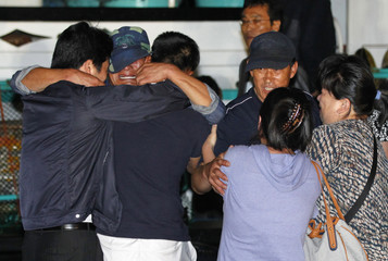 Crew members of a South Korean fishing boat, the 55 Daesung, meet their family members upon their return, at a port of the Sokcho Maritime Police in Sokcho