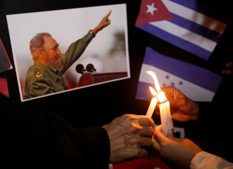 People place candles beside a picture of Fidel, as part of a tribute, following the announcement of the death of Cuban revolutionary leader Fidel Castro, in Tegucigalpa