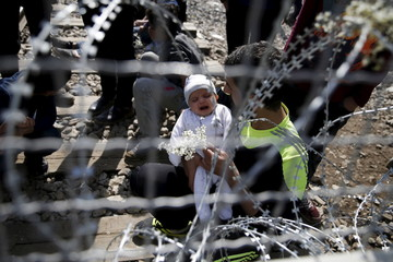 A migrant holds a baby as he sits next to the Greek-Macedonian border fence, near the Greek village of Idomeni