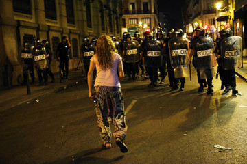 A demonstrator confronts riot police officers during clashes after a protest against government austerity measures in central Madrid