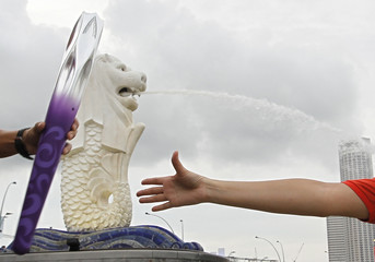 The Youth Olympic flame arrives in front of the Merlion statue in the Marina Bay area in Singapore