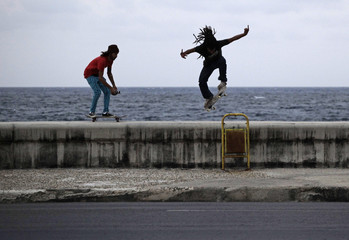 """A man jumps on skate board as another follows using a video camera on the ledge of Havana's seafront boulevard """"El Malecon\"""