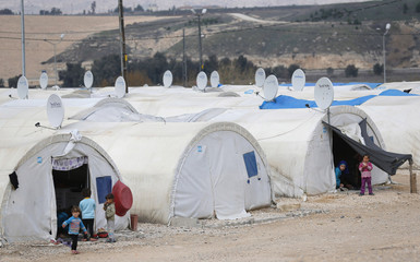 Syrian refugee children stand outside their tents at a refugee camp in Nizip in Gaziantep province, near the Turkish-Syrian border