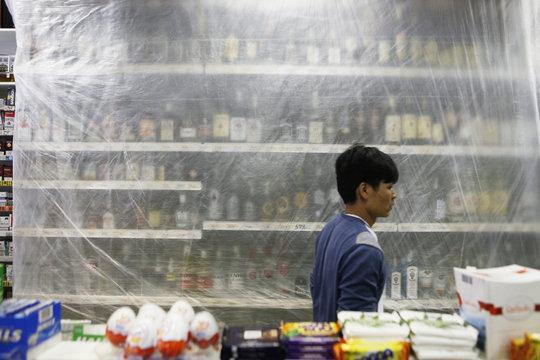 A vendor walks alongside covered shelves containing bottles of hard liquor in Prague