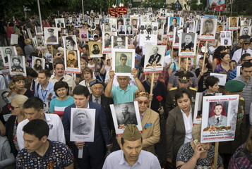 People carrying portraits of deceased relatives who took part in World War Two march in a parade during Victory Day commemorations in Almaty, Kazakhstan