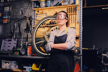 Portrait of female bicycle mechanic over tool stand background.
