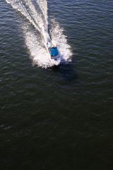 Motor boat with awning at high speed top view