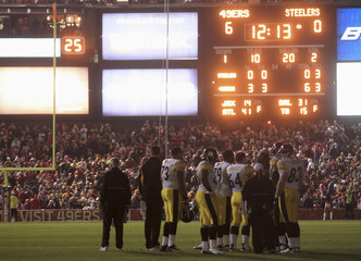 Pittsburgh Steeler players wait on the field in the dark after the stadium lights go out in San Francisco