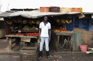 Karl Moi Okoth, a 27 year-old vegetable and fruit seller, poses for a picture in front of his makeshift shop in Nairobi's Kibera slum in the Kenyan capital