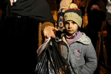A Syrian girl waits with her family as they depart after an aid convoy entered Madaya
