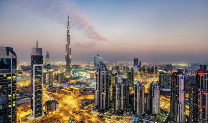Fantastic aerial view of Dubai, UAE, at sunset. Futuristic architecture of a big modern city in dramatic light. Colourful nighttime skyline. Travel background.