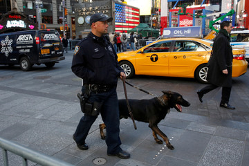 An officer with the NYPD Transit Bureau K-9 unit walks through Times Square in New York