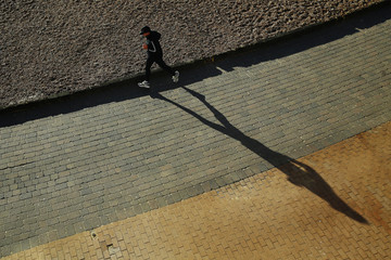 A jogger casts a shadow as he runs along the promenade at Brighton in southern England