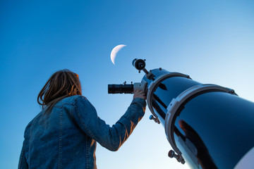 Girl looking at the Moon through a telescope. My astronomy work. Wall mural