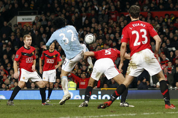 Manchester City's Tevez shoots to score against Manchester United during their English League Cup soccer match in Manchester