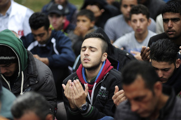 A Syrian migrant offers Eid al-Adha prayers outside the Sarayici oil wrestling arena in Edirne