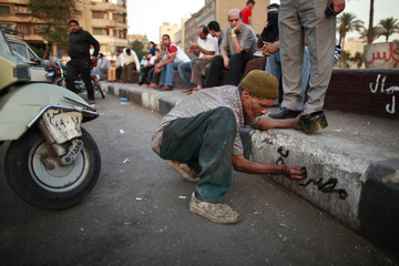 """A man writes """"Free Egypt"""" on the side of a pavement at Tahrir Square in Cairo"""