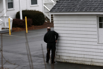 A police officer stands ready to draw his weapon outside a building being inspected by a Connecticut State Police SWAT team on the grounds of the St. Rose of Lima Catholic church in Newtown, Connecticut