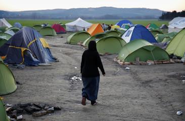 A stranded refugee walks through a camp by the Greek-Macedonian border near the Greek village of Idomeni