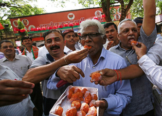 Supporters of Bharatiya Janata Party (BJP) distribute sweets, as they celebrate after learning of initial poll results outside their party office in  outside their party office in Mumbai