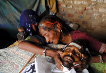 A woman mourns the death of a man who died after consuming bootleg alcohol in Tando Mohammad Khan in Pakistan