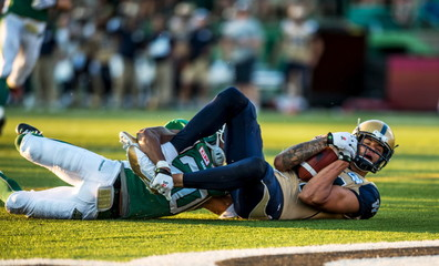 Winnipeg Blue Bombers slotback Nick Moore tackled by Saskatchewan Roughriders defensive back Maze during the second half of CFL football game in Regina