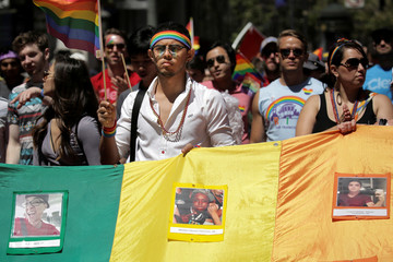 A marcher holds rainbow flag with photos of the victims of the Orlando mass shooting during the San Francisco LGBT Pride Parade in San Francisco, California