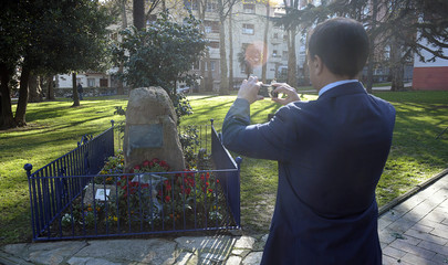A man takes a picture of red roses left next to a memorial for victims of armed Basque separatists ETA in the Uned Gardens in Portugalete