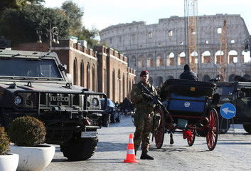 Armed Italian soldiers patrol at the Colosseum as emergency security measures continue ahead of New Year's eve celebrations in Rome
