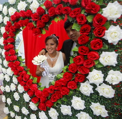 A couple poses for a picture after a mass wedding ceremony ahead of Valentine's Day celebrations in Lima