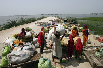 Residents of Khairpur Nathan wait for transport on a road to move to a safer place after floodwaters completely submerged their village