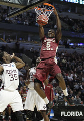 James of Florida State slam dunks over Turner and Roberson of A&M during their NCAA basketball game in Chicago