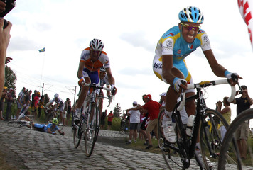 Astana rider Alberto Contador of Spain cycles on a cobblestone sector while a rider falls during the third stage of the Tour de France cycling race between Wanze and Arenberg-Porte Du Hainaut