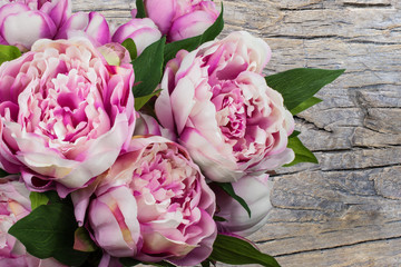 Summer bouquet with pink peony flowers isolated on rustic wooden background.
