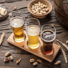 Wall Mural - Glasses of beer and snacks on the wooden table.