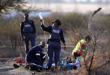 A paramedic receives help from a policewomen as he tends to the injured after protesting miners were shot outside a South African mine in Rustenburg