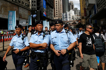 Policemen patrol during a march to demand universal suffrage, on the day marking the 19th anniversary of Hong Kong's handover to Chinese sovereignty from British rule, in Hong Kong