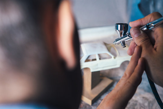 Unrecognizable man airbrushing slot car