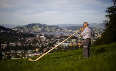 Alphorn maker Stocker checks an alphorn in his garden outside his factory in Kriens, central Switzerland