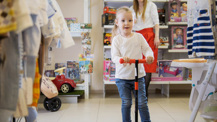 Sweet little girl riding a scooter in a children's store