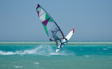 Recreational water sports: windsurfing. Windsurfer surfing waves and jumping high in the sea on a windy day. Extreme sports action with wind and water. Recreational sporting activity