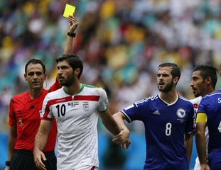 Iran's Ansarifard is shown the yellow card by referee Carballo of Spain past Bosnia's Pjanic during their 2014 World Cup Group F soccer match at the Fonte Nova arena in Salvador