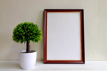 Picture frame with wooden pots on white wooden table